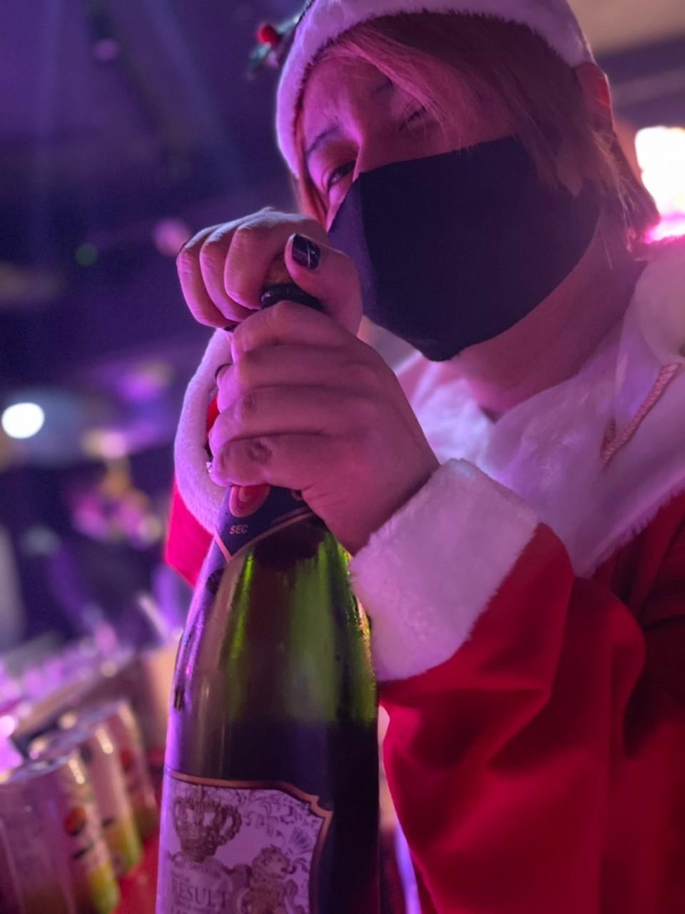 サンタコスプレでシャンパンを開ける李亜